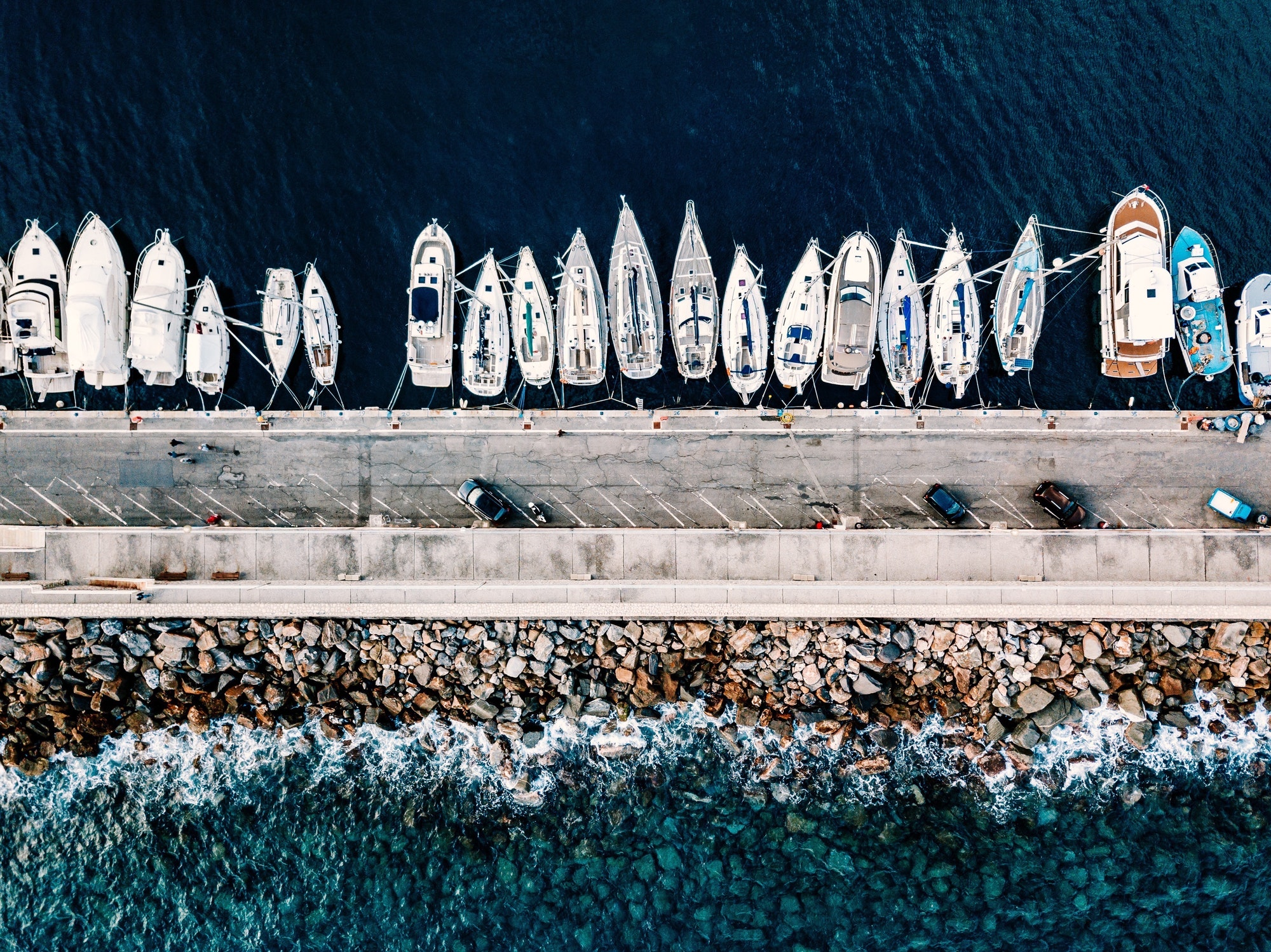 Aerial view of marina with boats and yachts in Italy. Blue sea landscape with white yachts top view