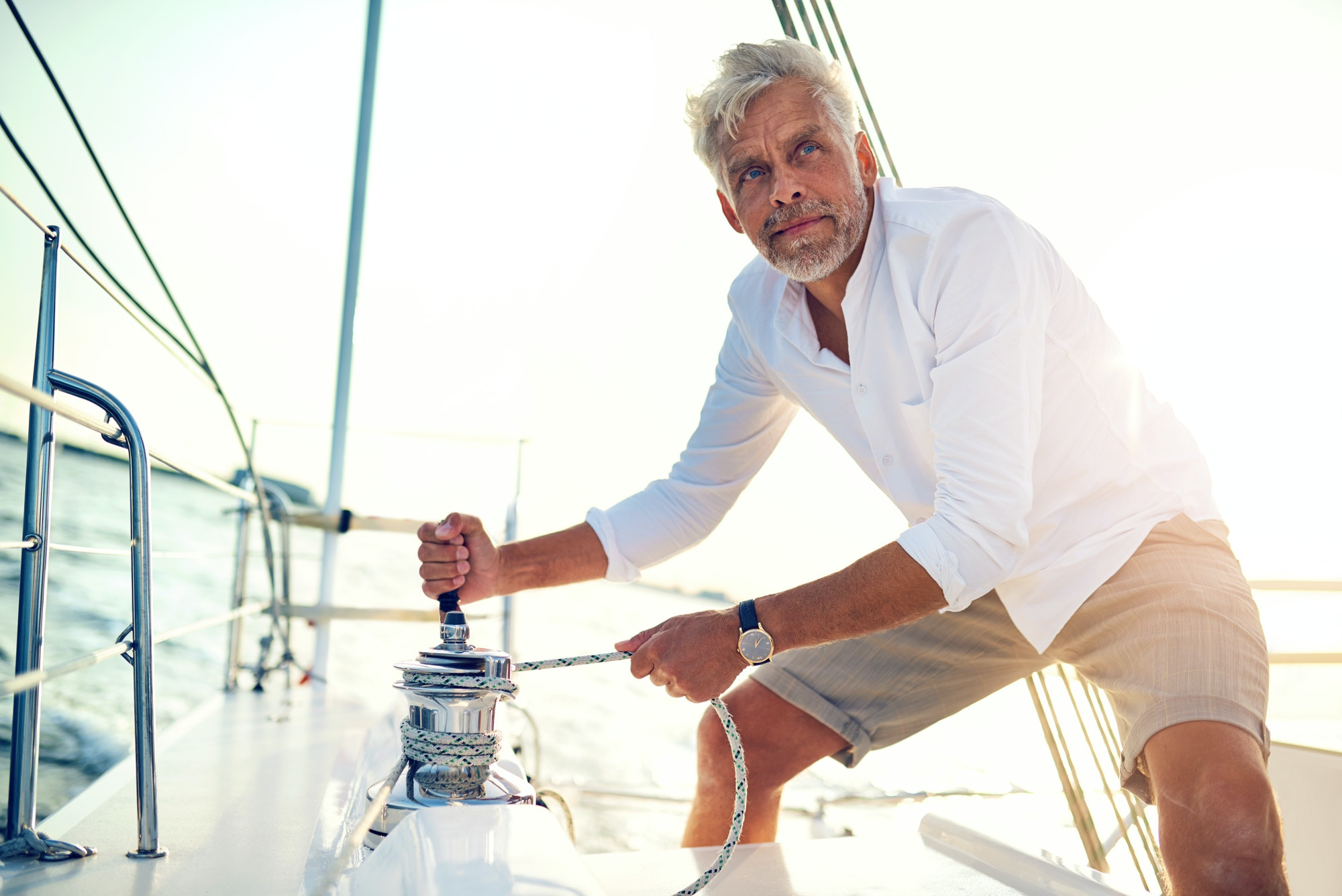 Mature man using a winch while out sailing